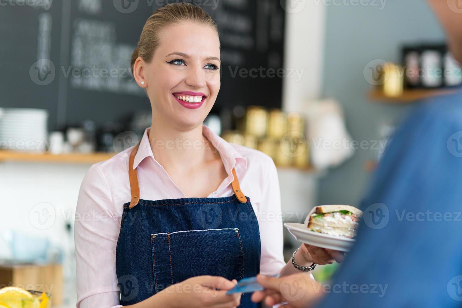 serveerster die klant dient bij de koffiewinkel foto
