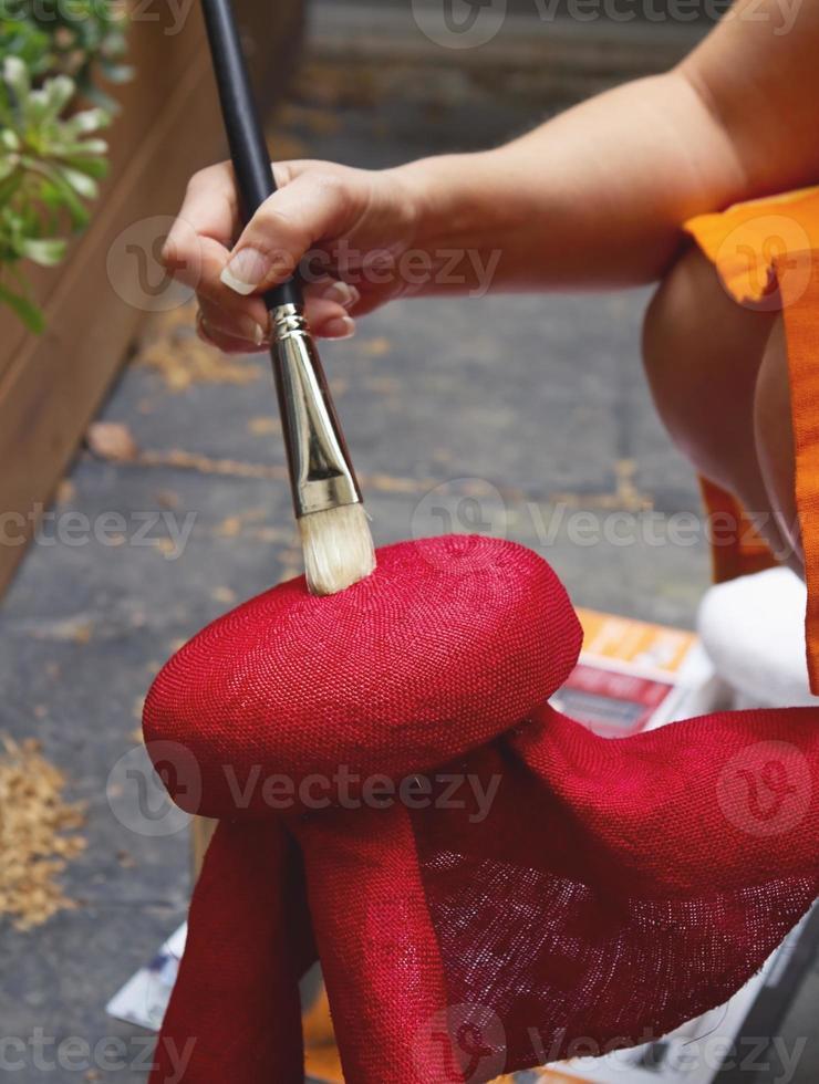 hoedenmaker borstelen verstijvingsoplossing op hoedenblok foto