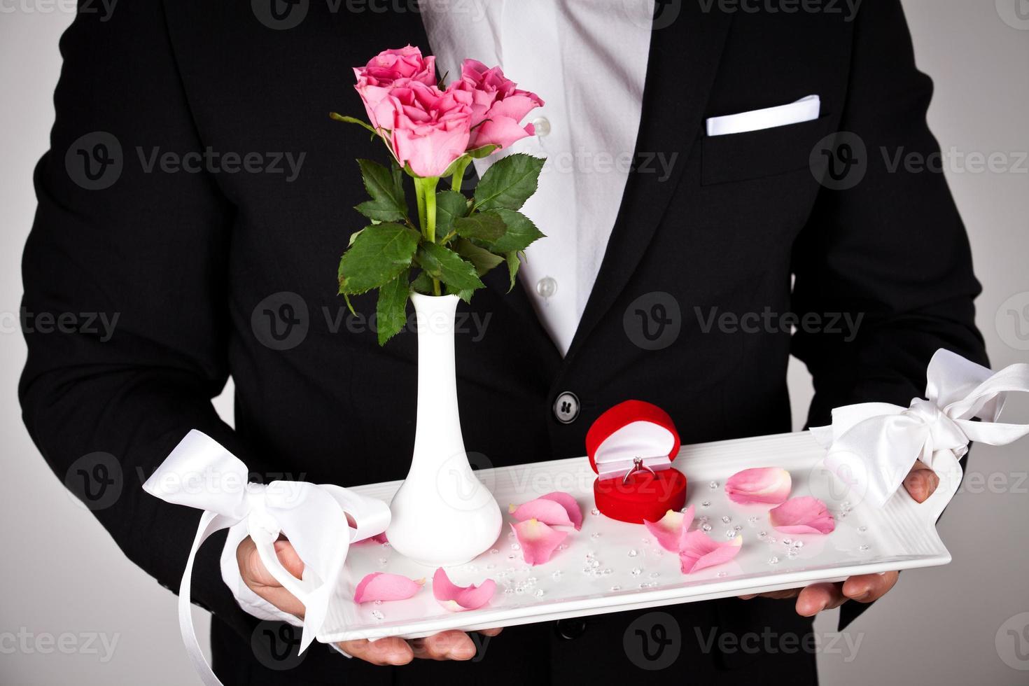 man in formele slijtage met verlovingsring en bloemen foto