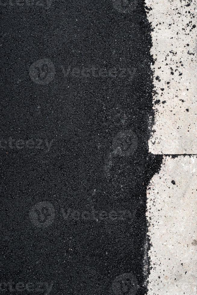 nieuw asfaltbeton bij de betonnen stoeprand foto