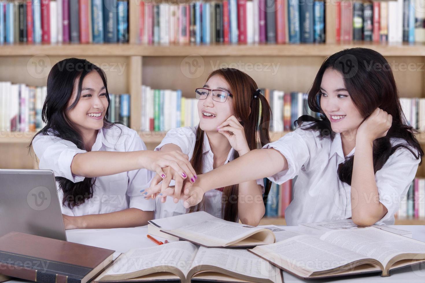 studenten stapelen hun handen op in de bibliotheek foto