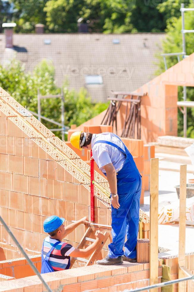 werknemer muren op de bouwplaats controleren foto