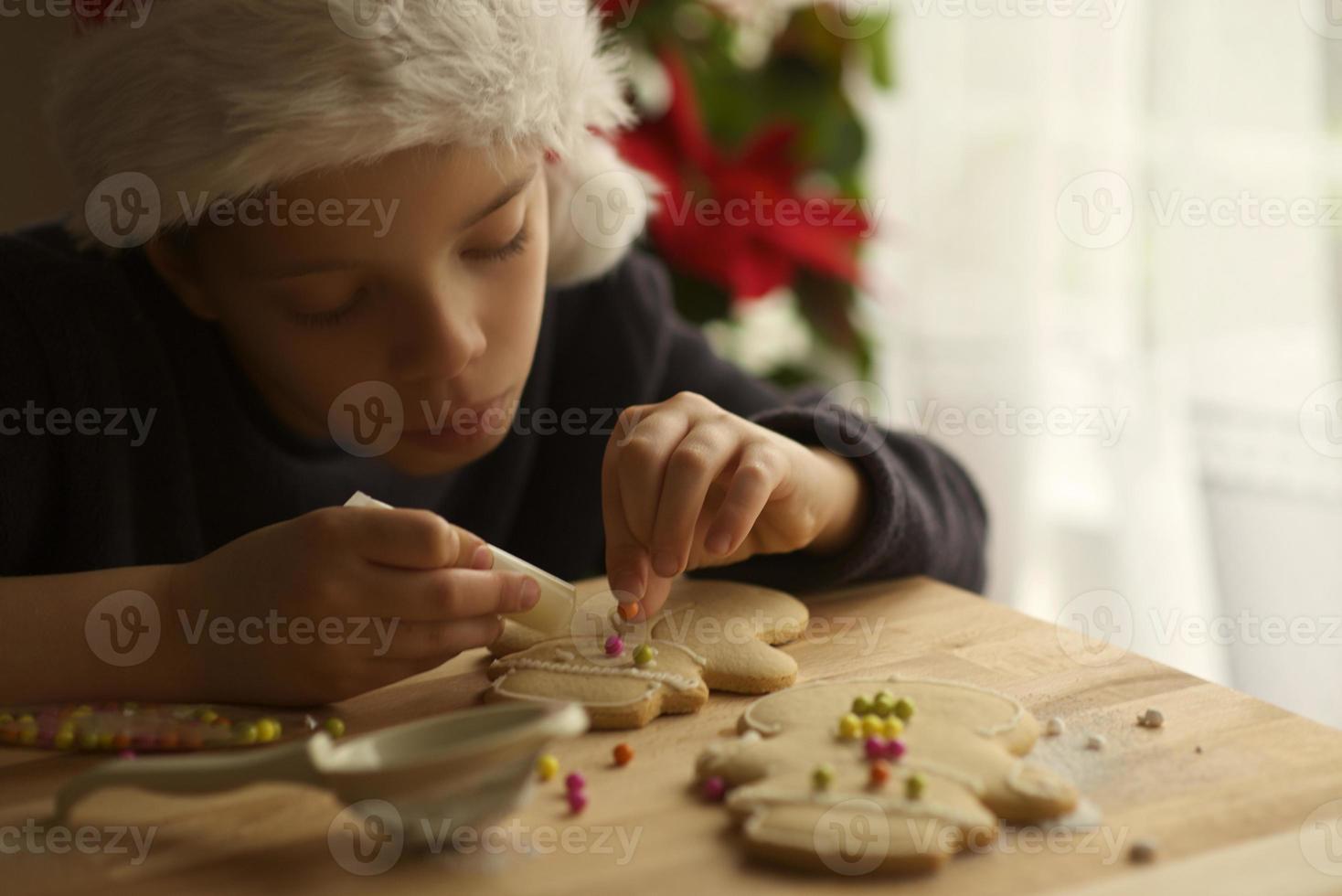 geconcentreerd kind bereidt peperkoekman voor op Kerstmis foto