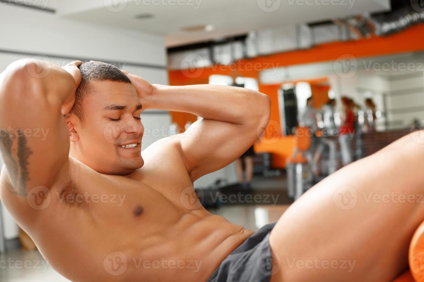 jonge aangename man doen buik crunches in de sportschool foto