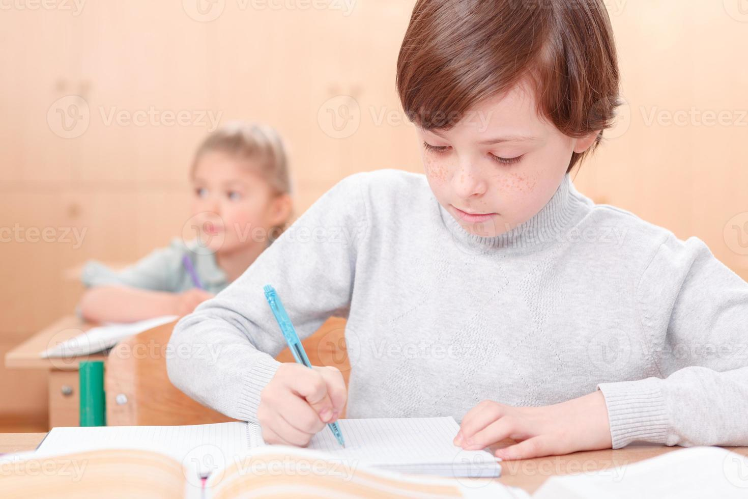 het schrijven van kleine jongen tijdens de lessen foto