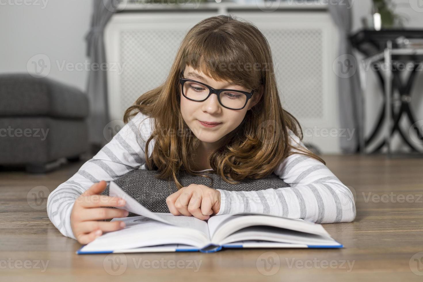 het boek van de tienerlezing terwijl thuis het liggen op vloer foto