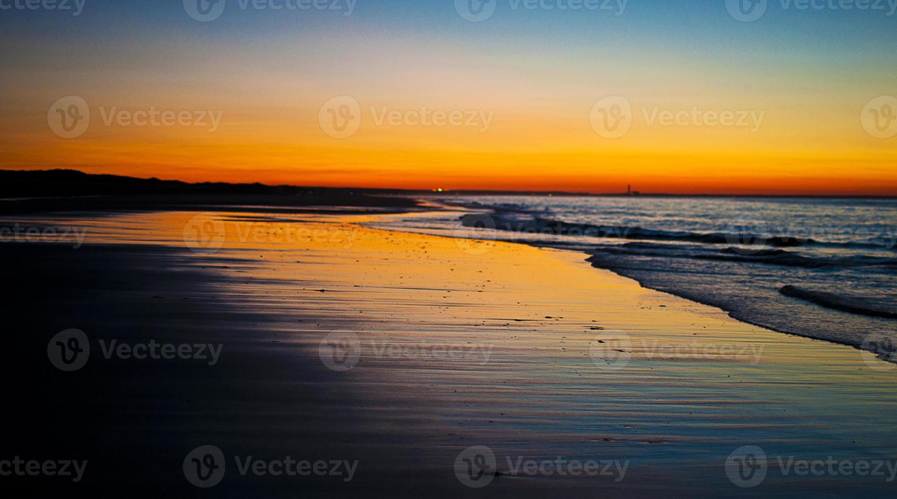 zonsondergang op zandstrand nek strand foto