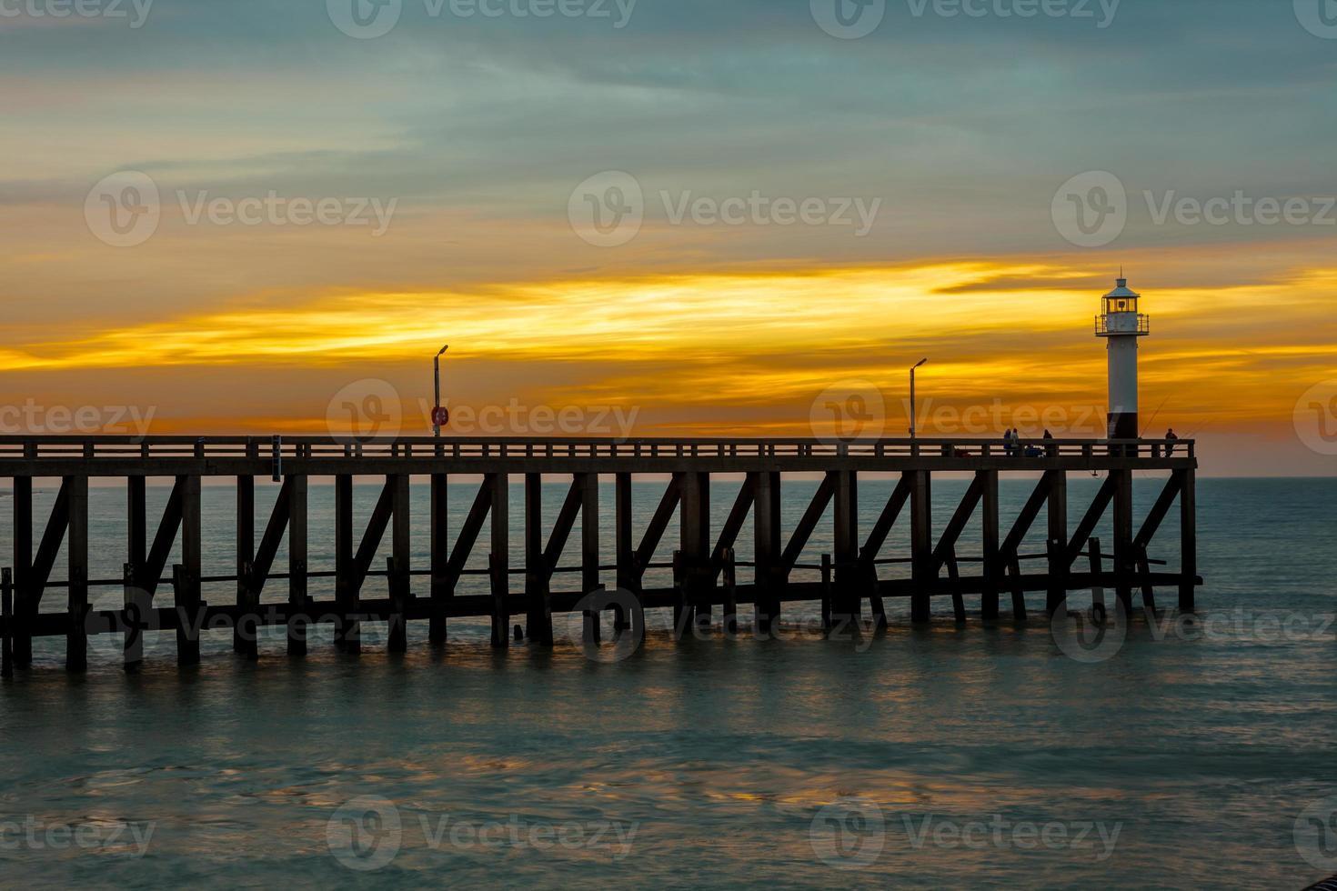 de pier met lichtmast aan zee foto