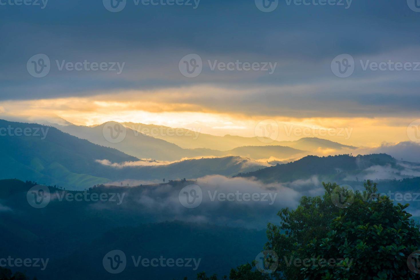 zon schijnt door de wolken met silhouetten van mountians foto