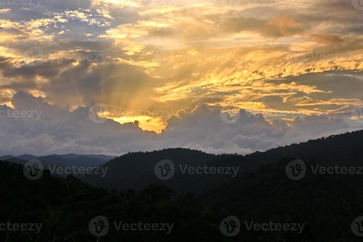zon schijnt door wolk boven berg foto