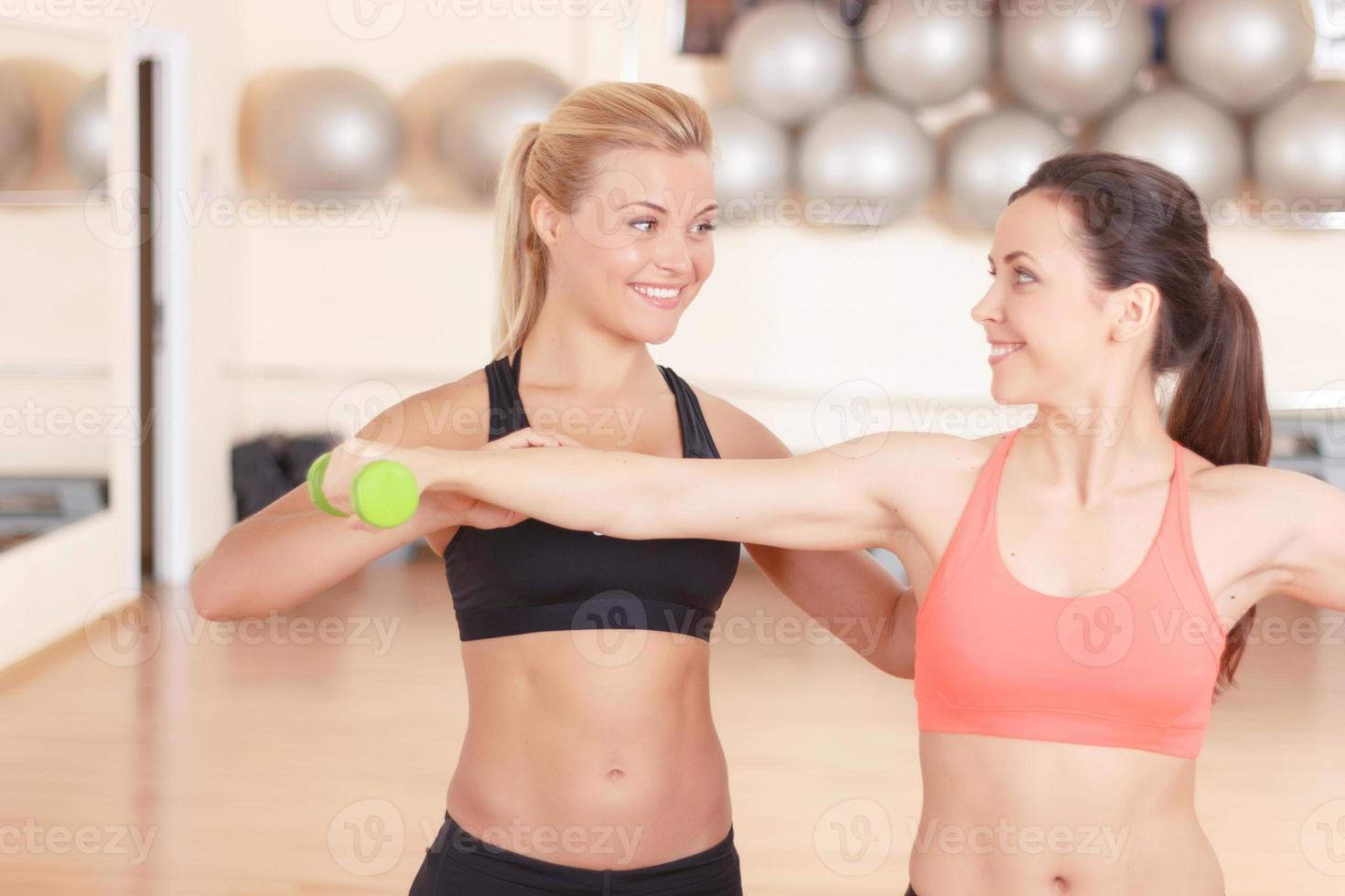 fitness instructeur helpt vrouw in de sportschool foto