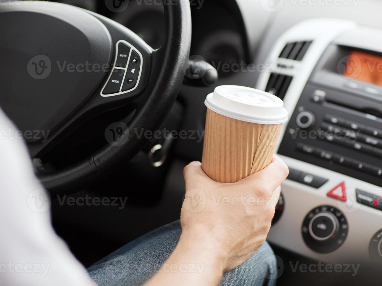 man met een to-go kopje koffie tijdens het rijden foto