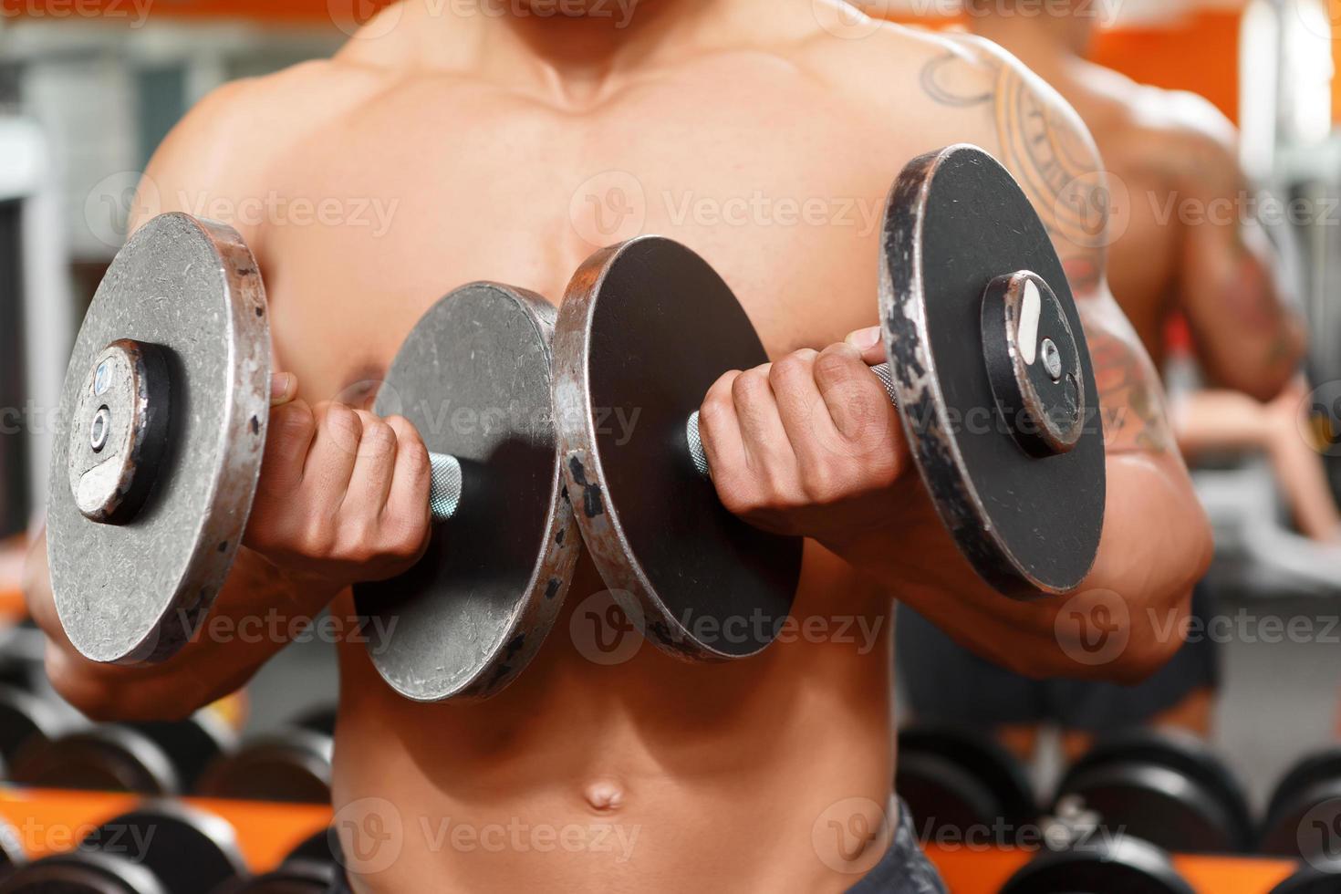 man tillen van twee halters in gym foto