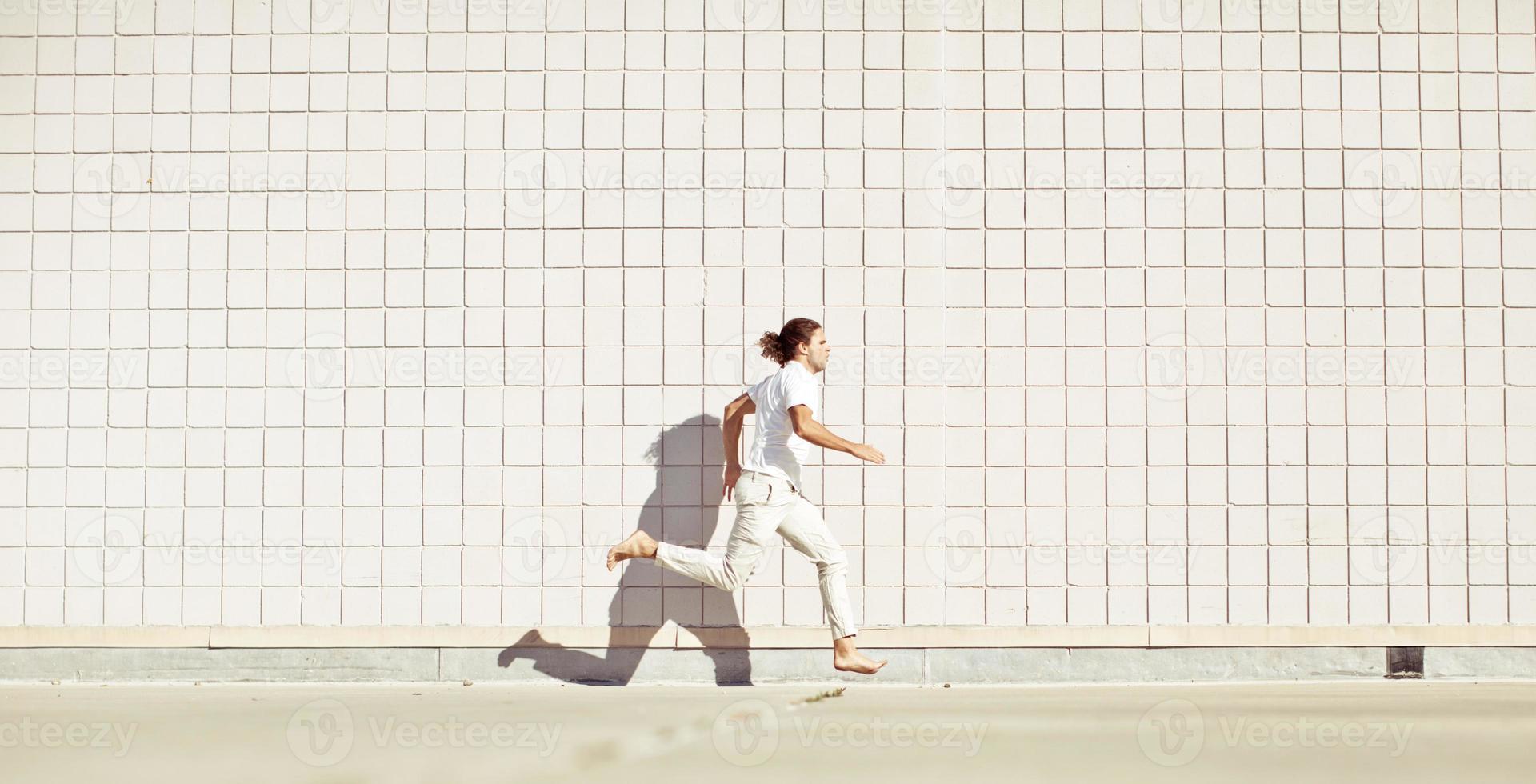 op blote voeten vrije hardloper (parkour atleet) helemaal in het wit gekleed foto