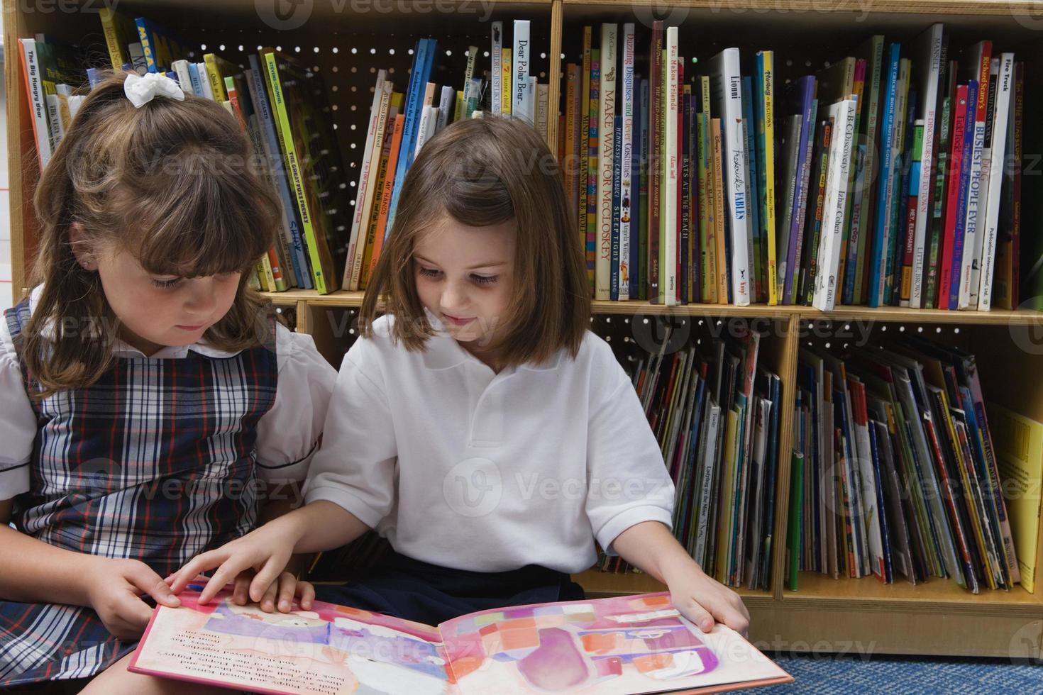 twee kinderen lezen samen op de vloer in een bibliotheek foto
