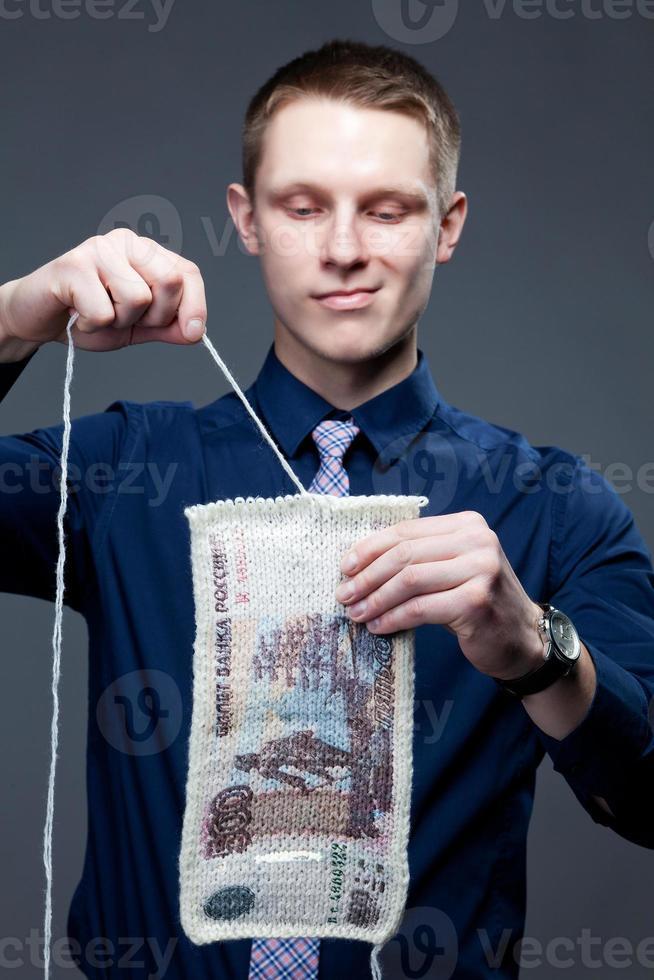 zakenman ontbindt het 500-bankbiljet als een gebreide stof foto
