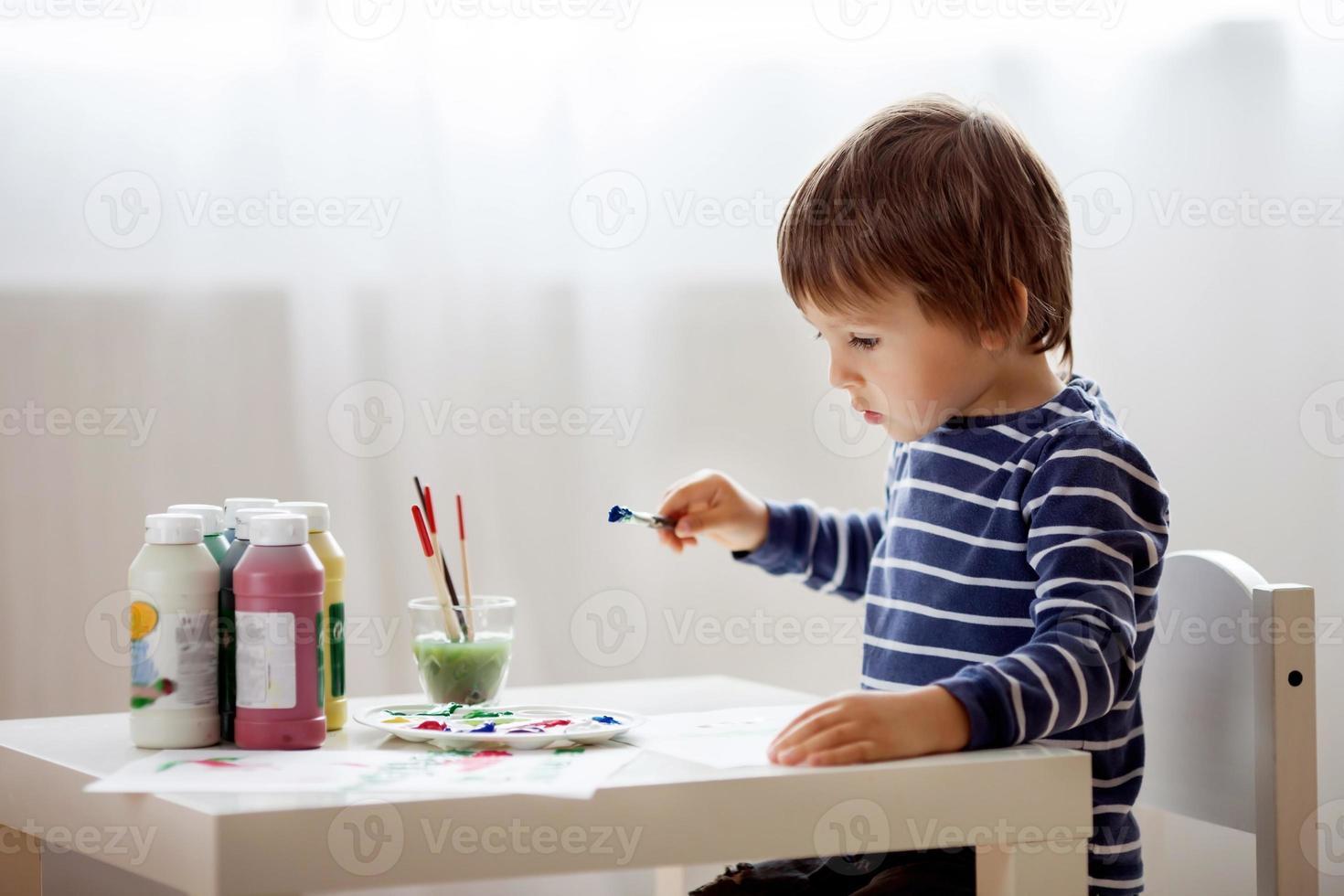 schattige kleine jongen schilderen in zijn album foto