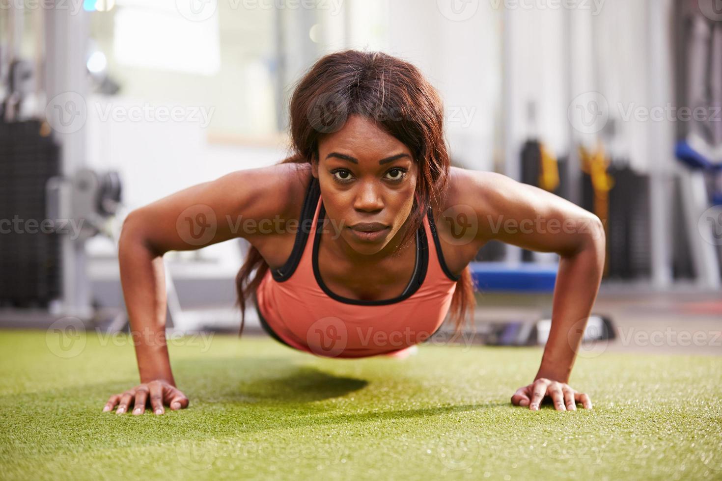 jonge vrouw doet push-ups in een sportschool foto