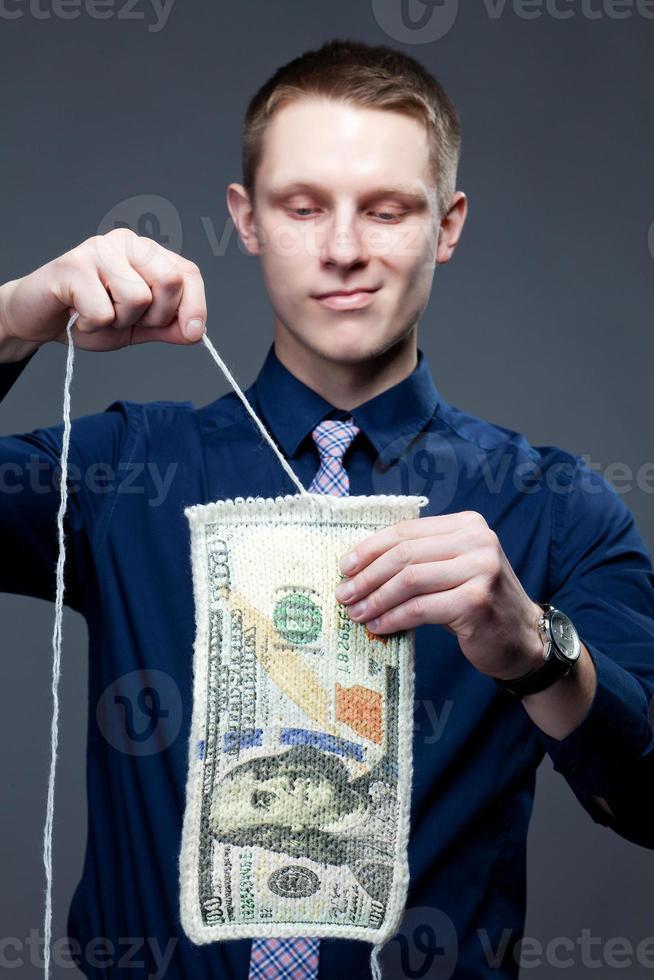 zakenman ontbinden het 100-bankbiljet als een gebreide stof foto