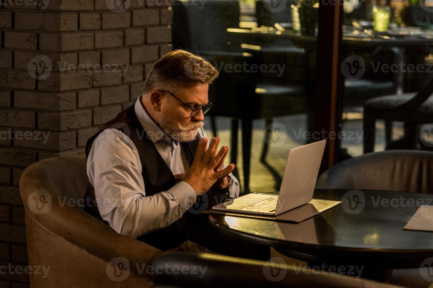 zijaanzicht van peinzende senior zakenman kijken laptop scherm in café foto