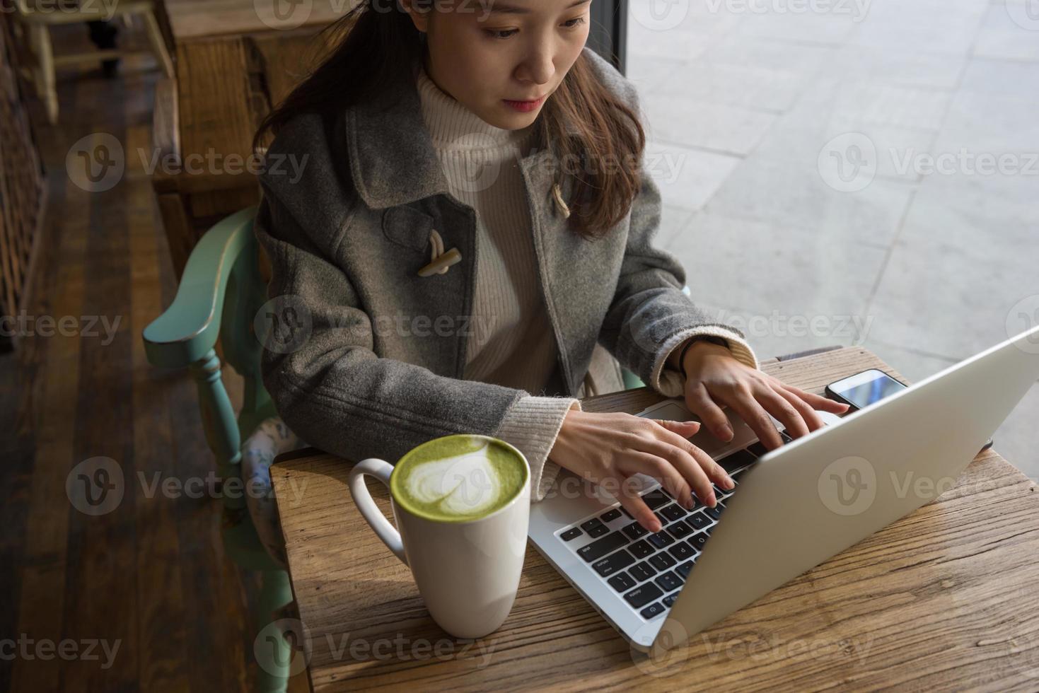 vrouw met matcha koffie met behulp van laptop foto