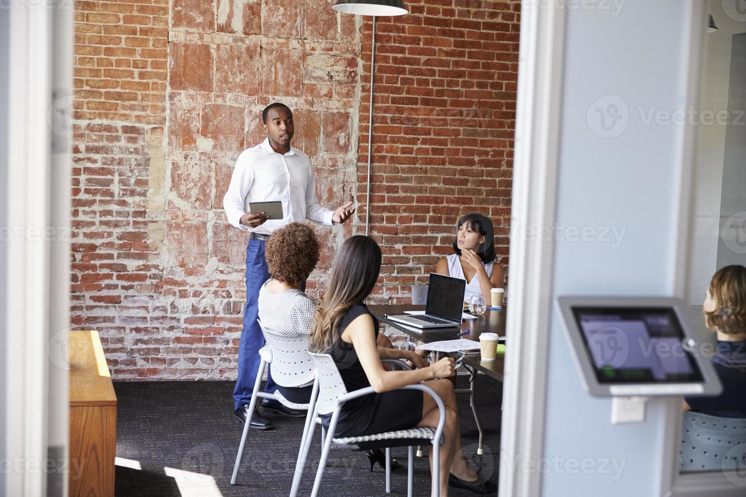 zakenman permanent om boardroom vergadering aan te pakken foto