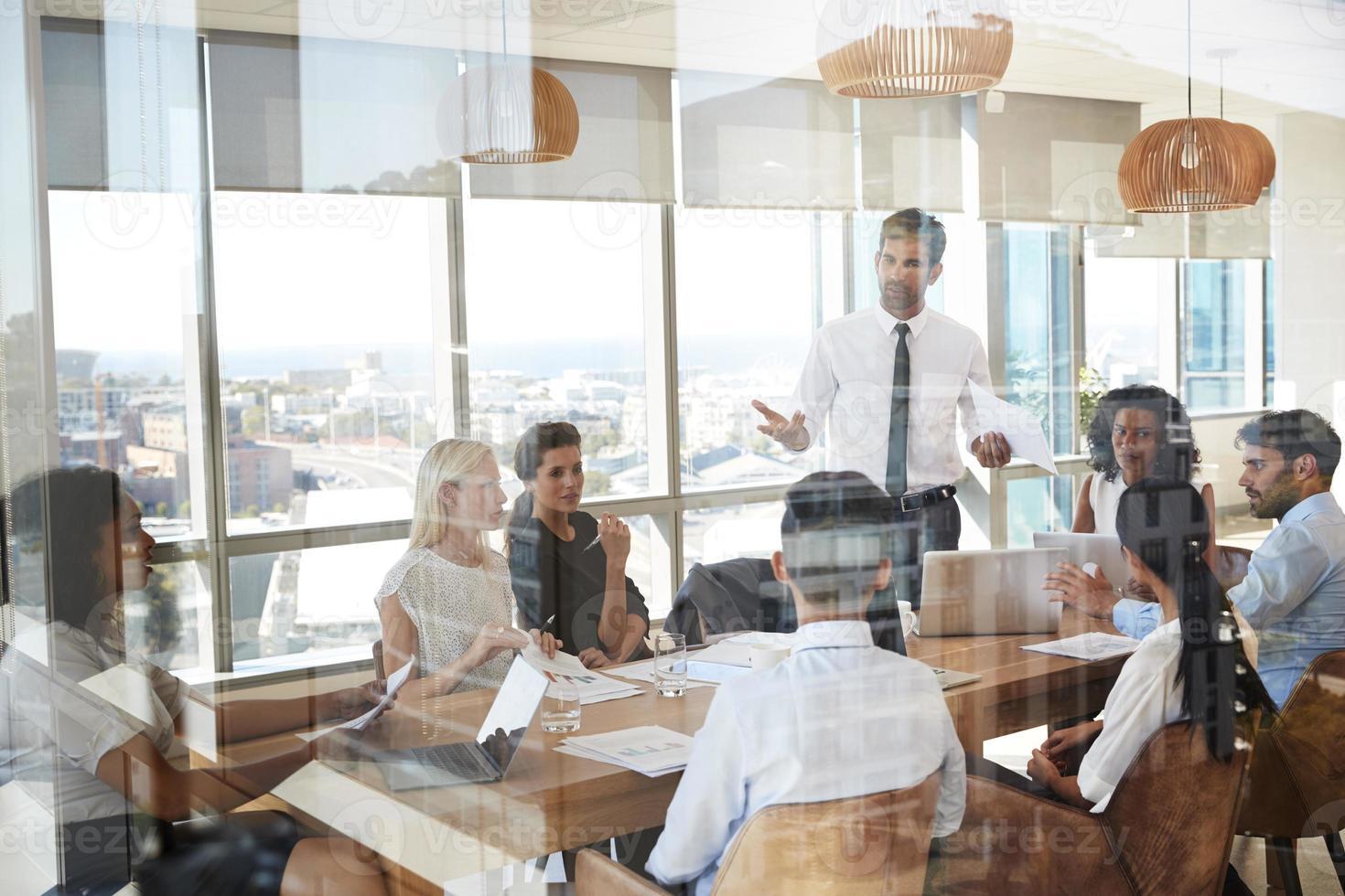 zakenman leidt vergadering rond tafel schot door deur foto