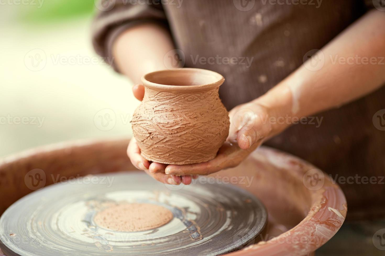 handen bezig met aardewerk wiel foto