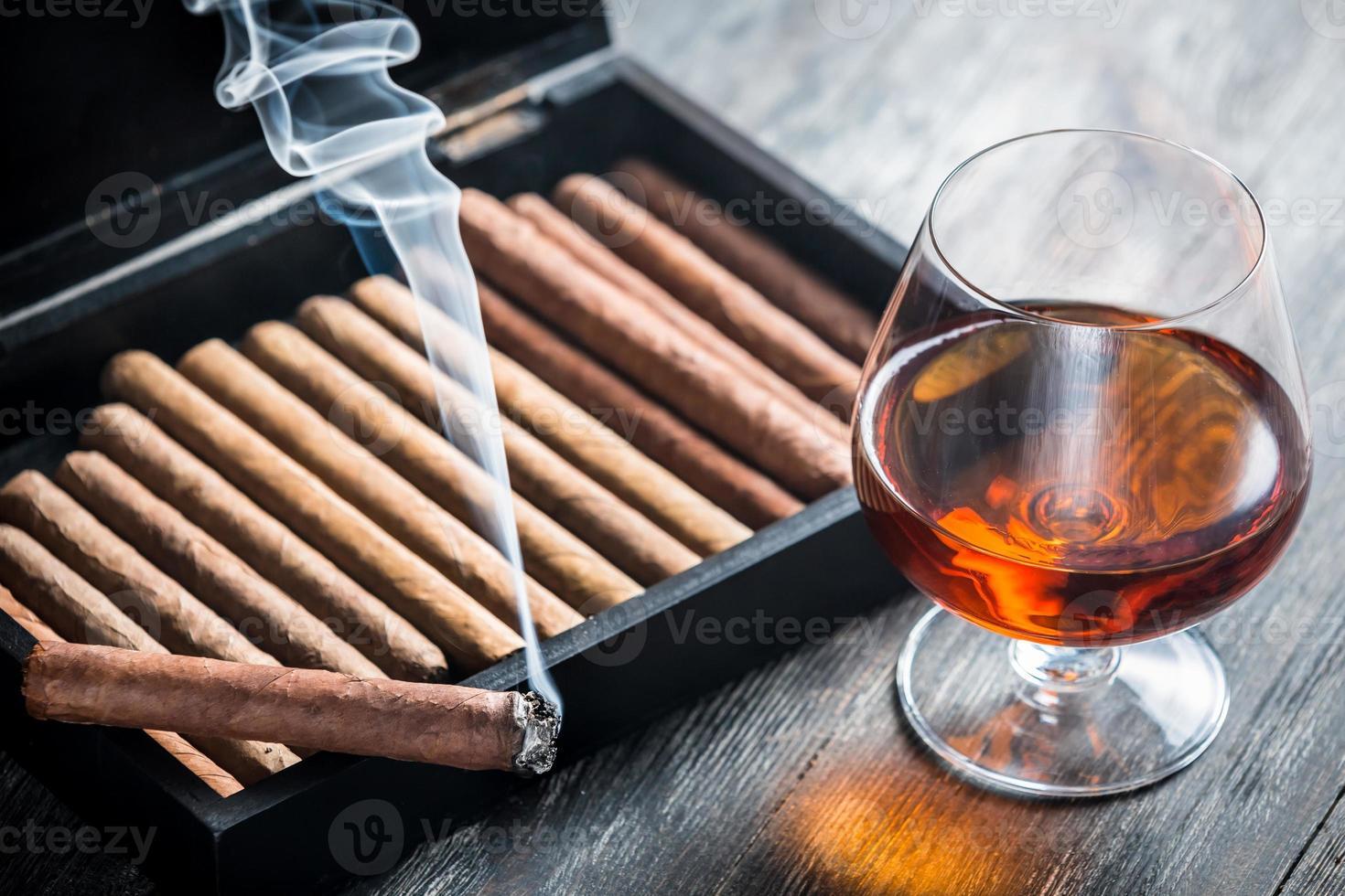 brandende sigaar en cognac in glas foto