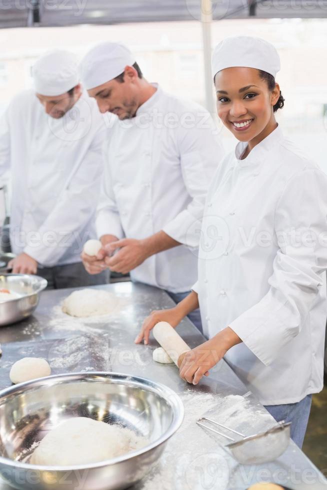 team van bakkers werken aan balie foto