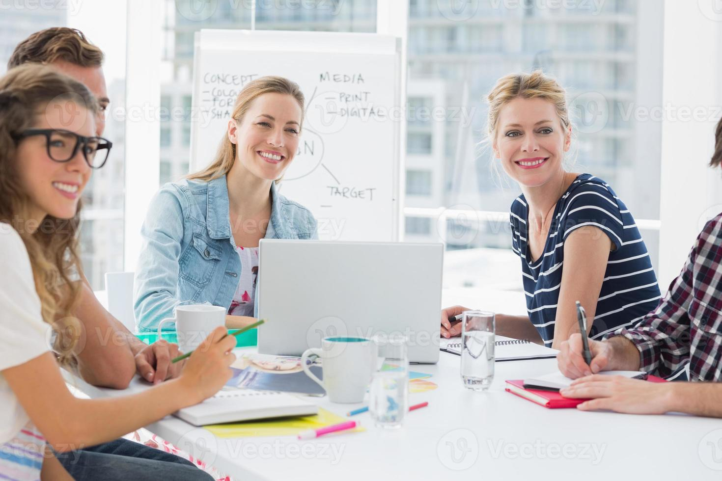 casual zakenmensen rond vergadertafel in kantoor foto