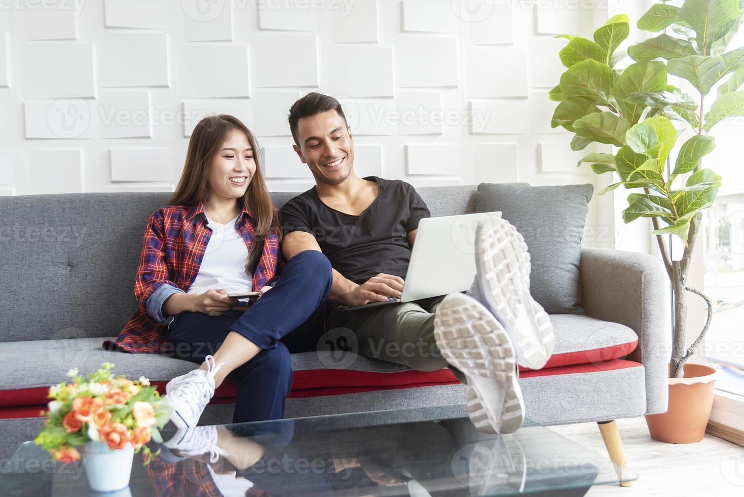 paar met behulp van internet om te werken in de laptop in de woonkamer. netwerkverbindingstechnologie voor het leven. foto