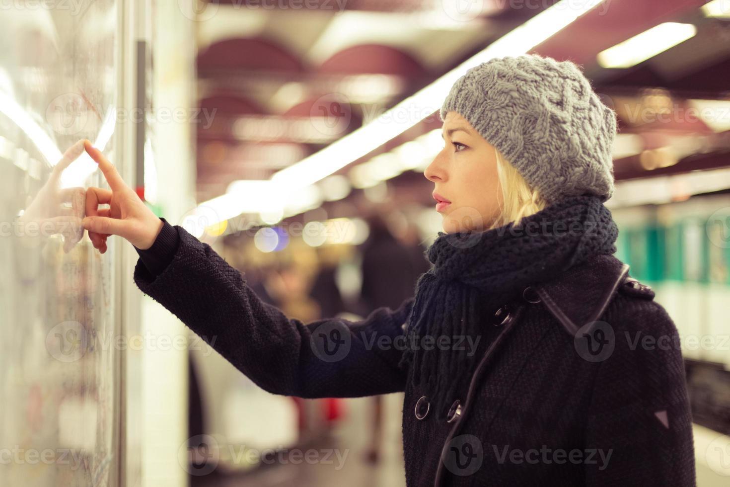 dame die op het paneel van de kaart van het openbaar vervoer kijkt. foto