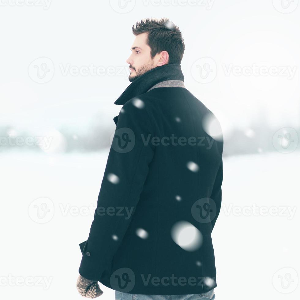 knappe elegante man die buiten in de winter sneeuwstorm foto