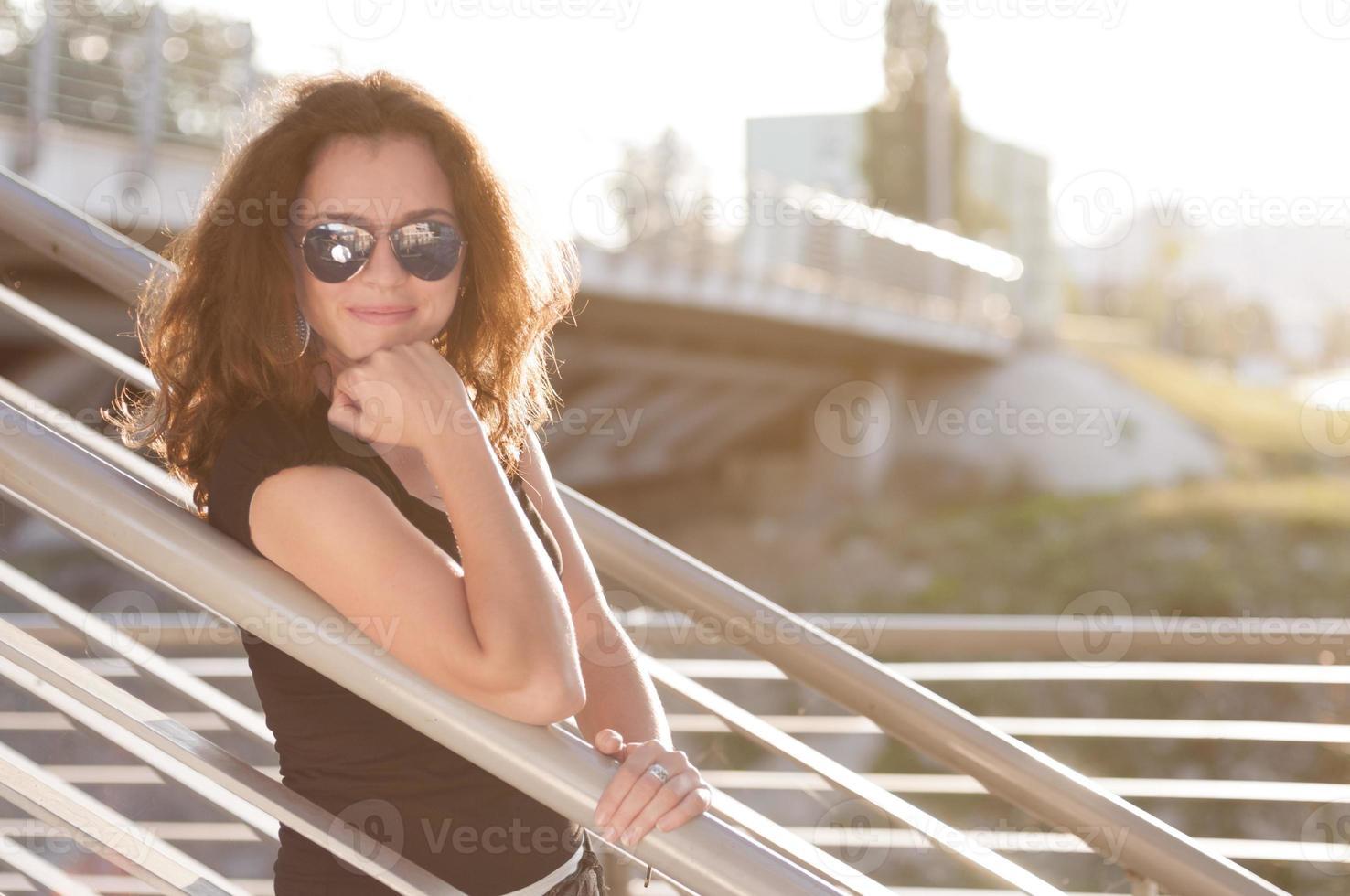 mooie lachende jonge vrouw leunend op een hek foto