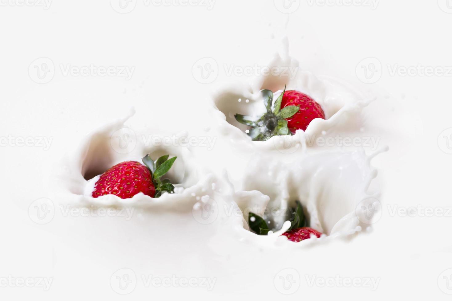drie aardbeien spatten in de melk. foto
