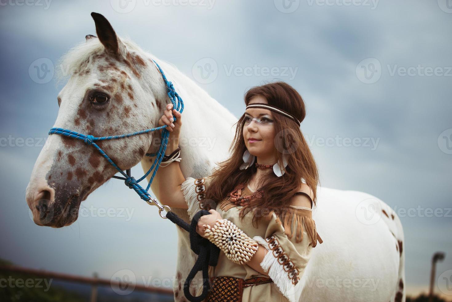 Indisch meisje met wit paard op hemelachtergrond foto