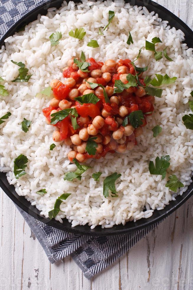 rijst met kikkererwten en peterselie close-up. verticaal bovenaanzicht foto