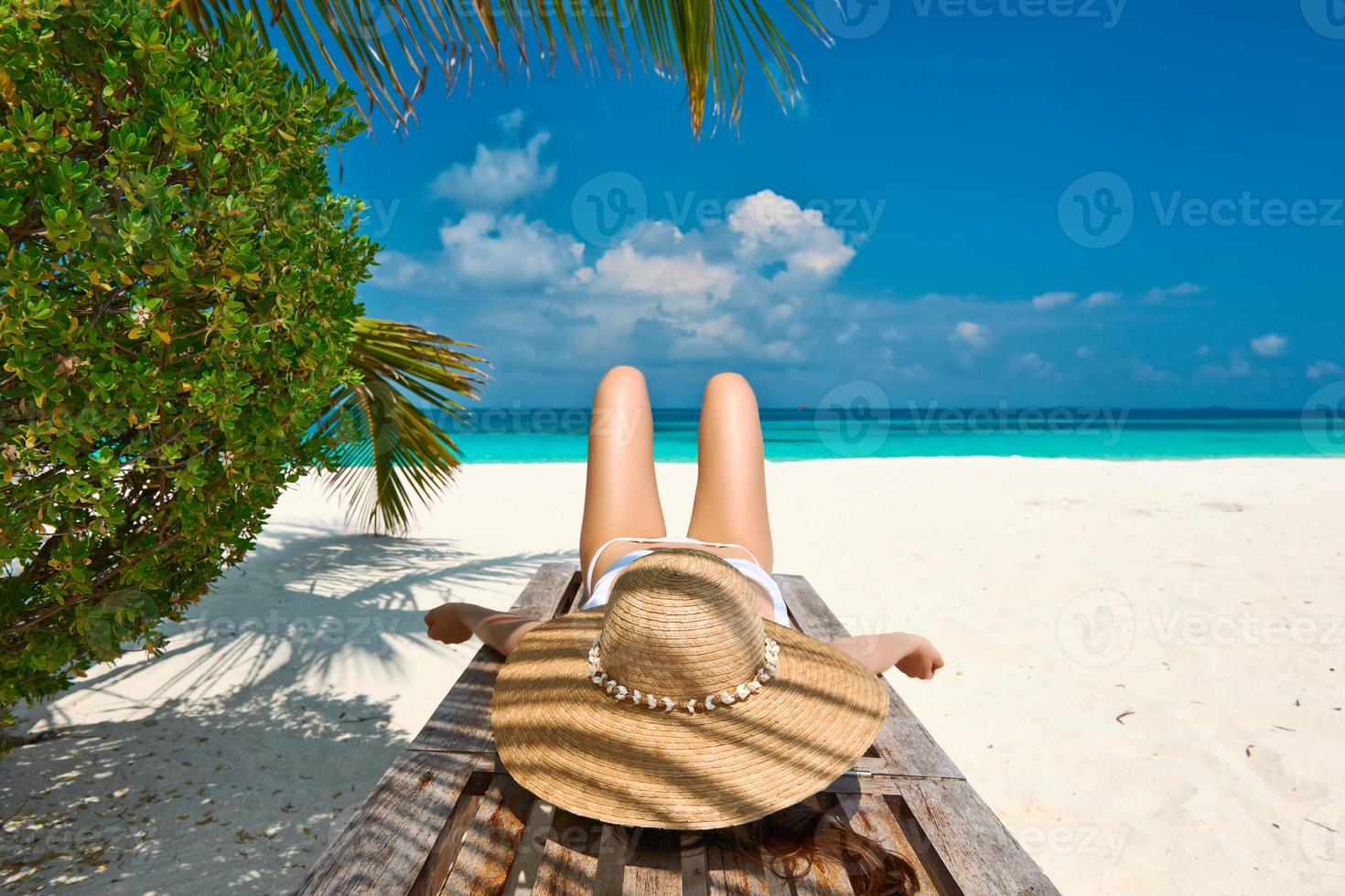 vrouw op strand liggend op chaise lounge foto