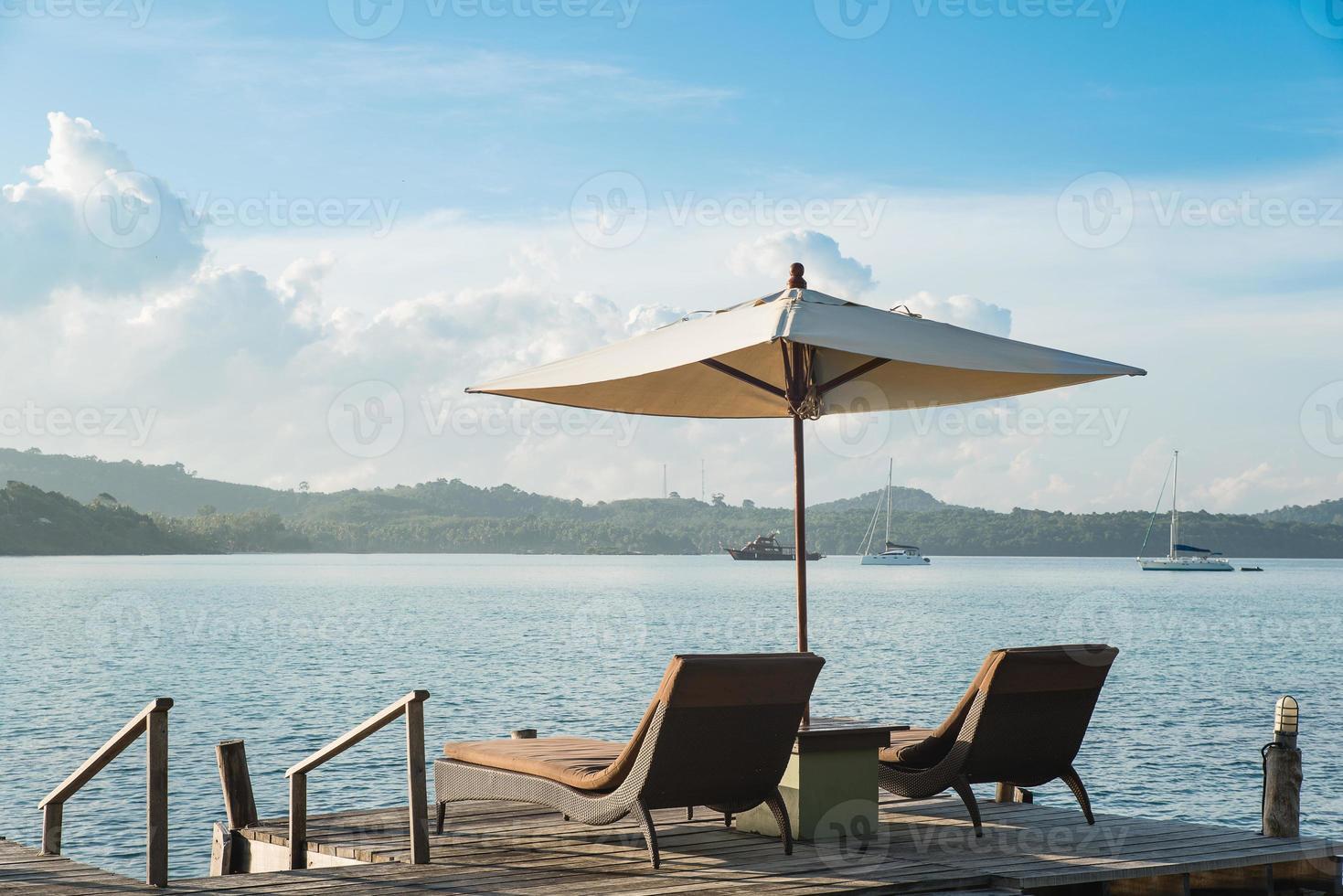 twee stoelen en paraplu op houten bureau tegen blauwe hemel foto