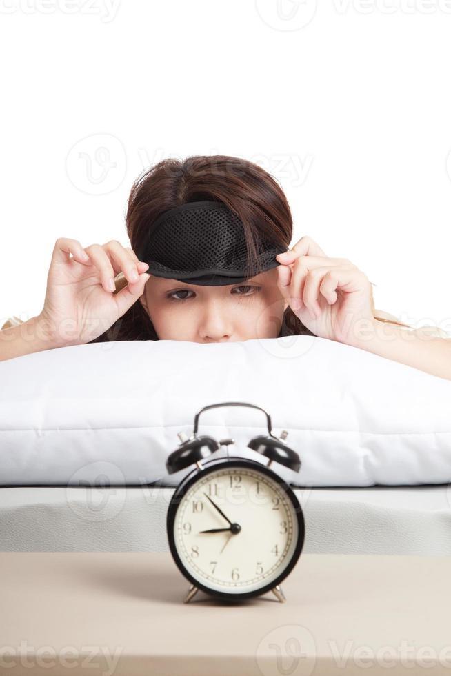 slaperig Aziatisch meisje met oogmasker en wekker foto