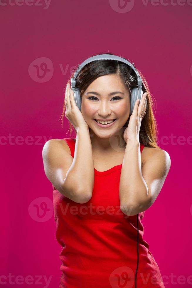 gelukkige Aziatische vrouw die aan muziek op hoofdtelefoons luistert. foto