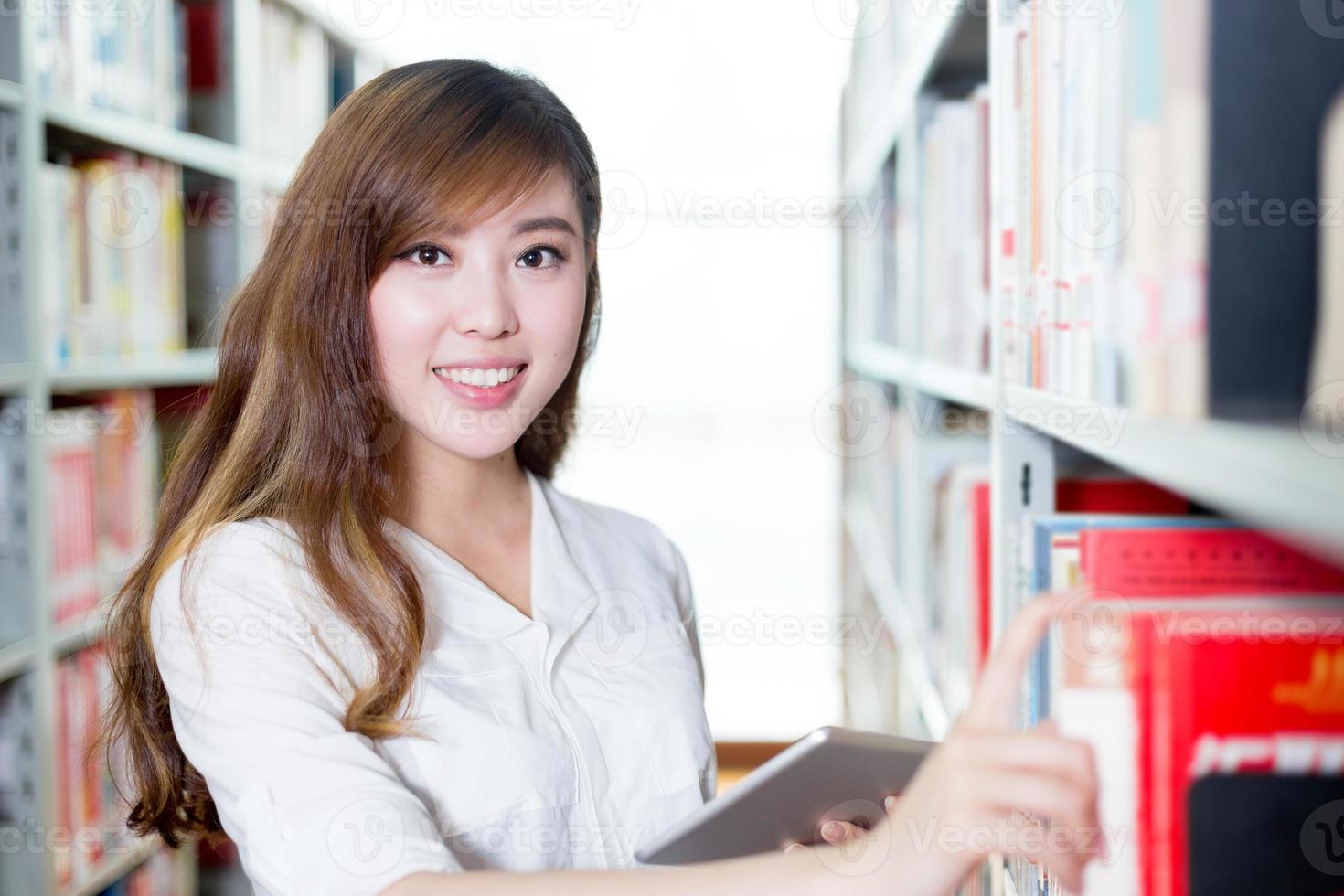 Aziatische mooie vrouwelijke student die tablet in bibliotheek gebruiken foto