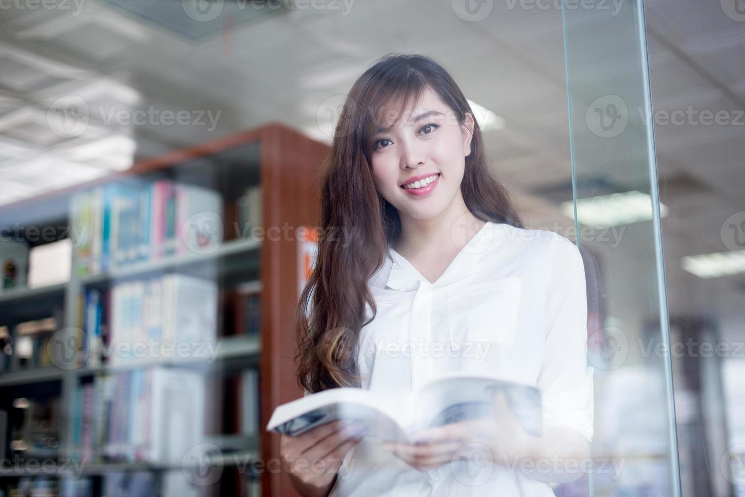 Aziatische mooie vrouwelijke student met boek in bibliotheek portret foto