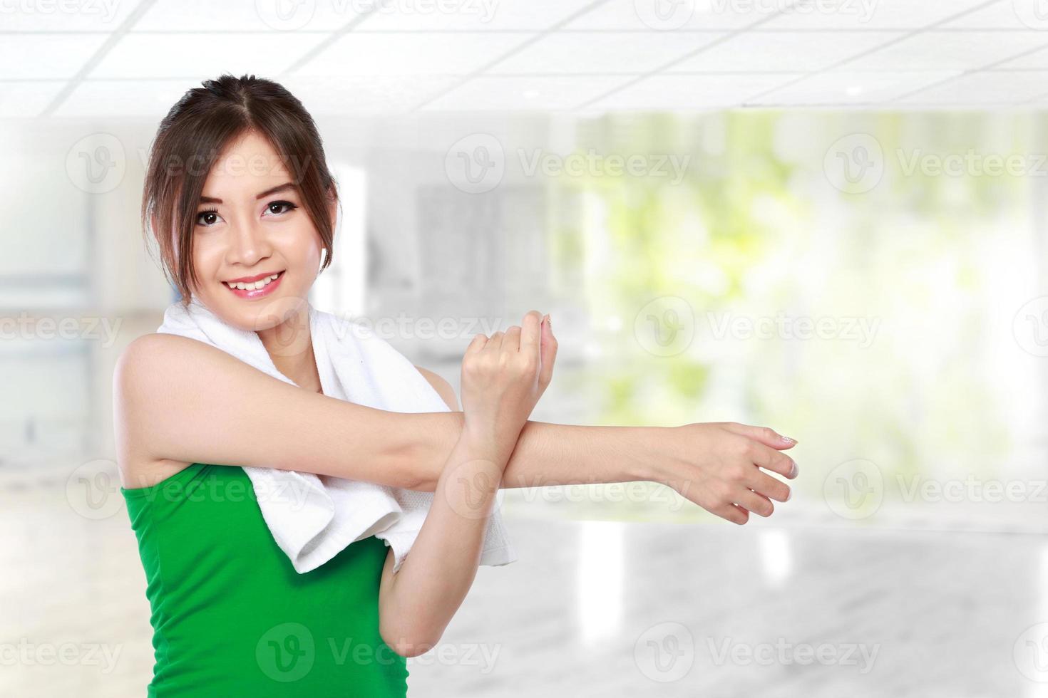 vrouw doen die zich uitstrekt in de sportschool foto