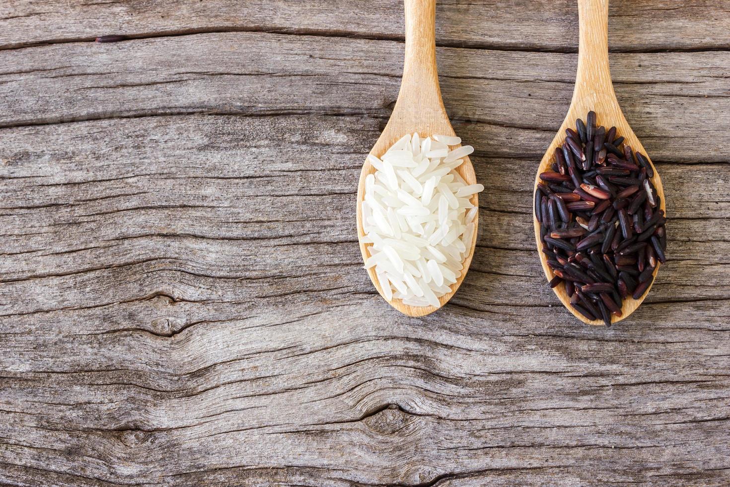 ongekookte rijst in lepel, witte en zwarte rijst. foto