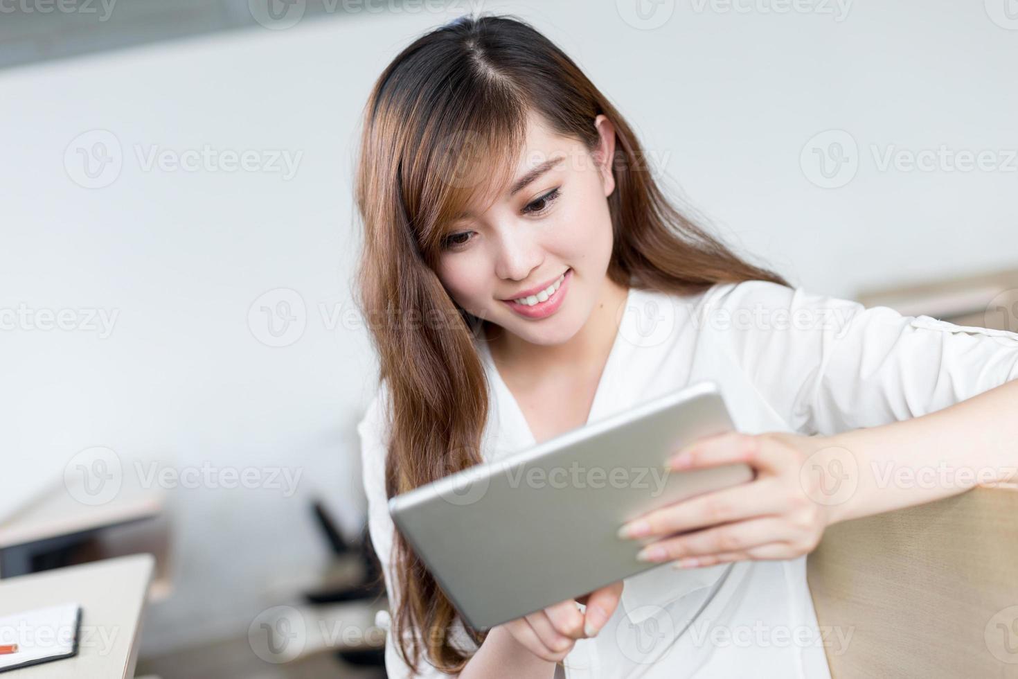Aziatische mooie vrouwelijke studentenstudie met tablet in klaslokaal foto