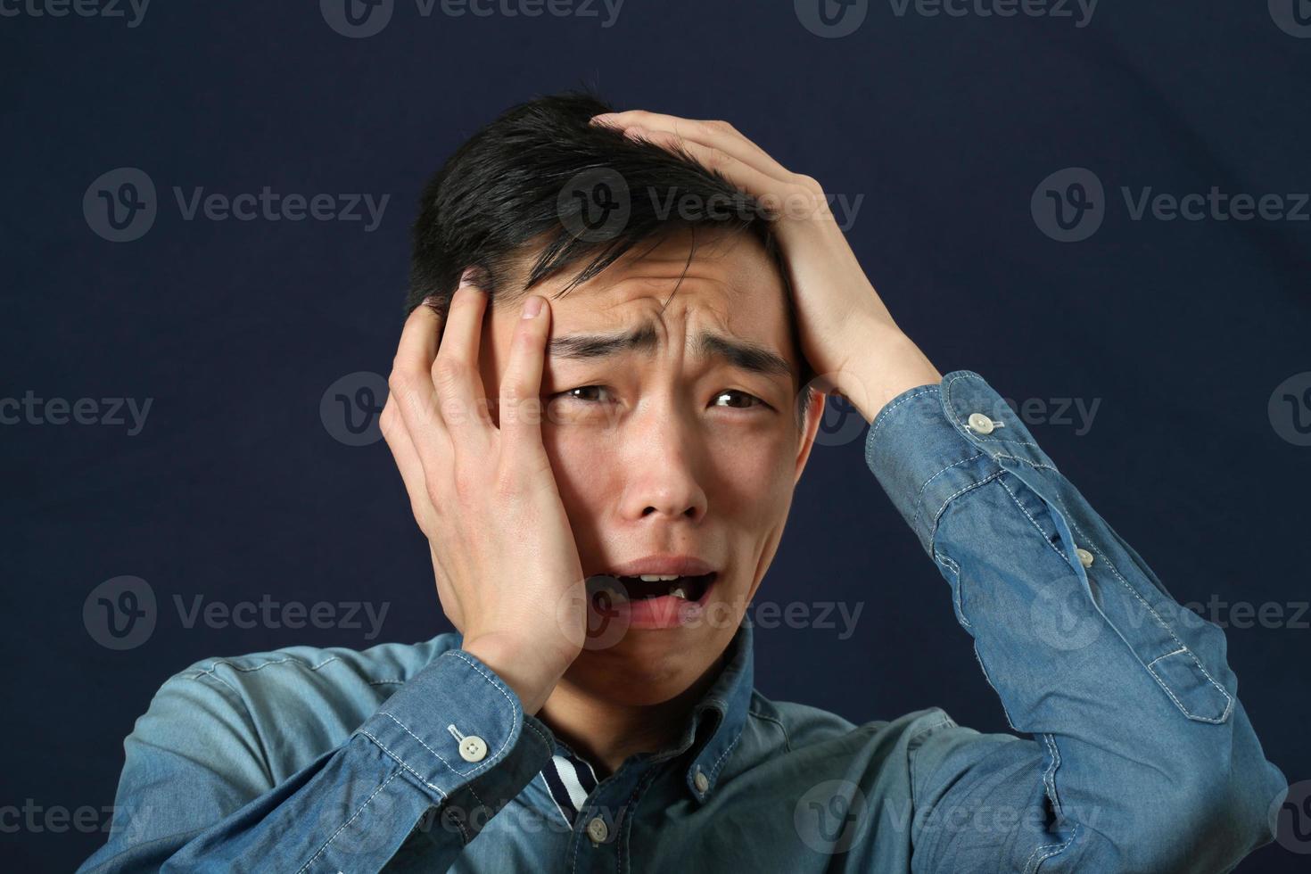 teleurgesteld jonge Aziatische man huilen en zijwaarts op zoek foto
