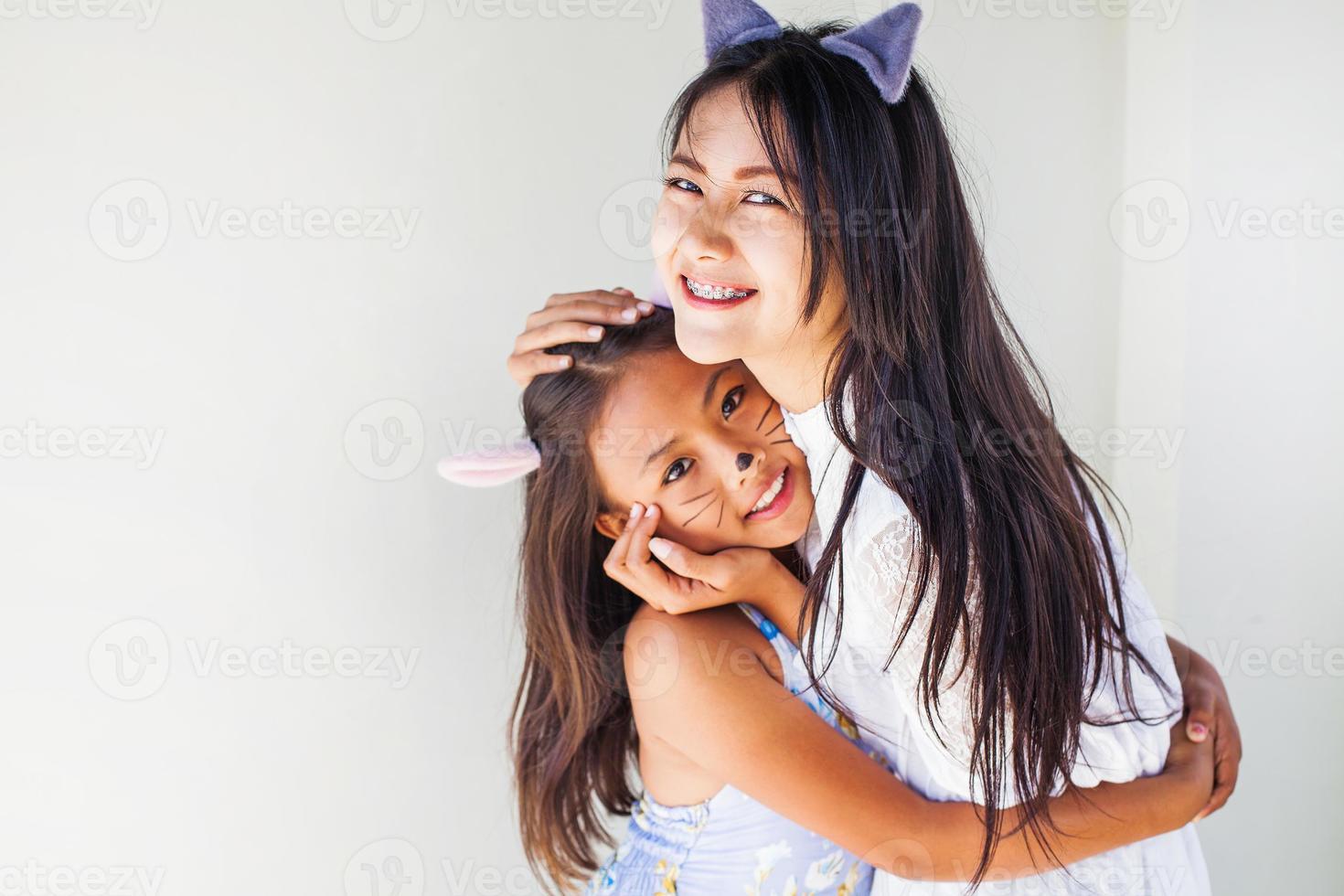 twee Aziatische meisjes gekleed het dragen van kattenoren foto
