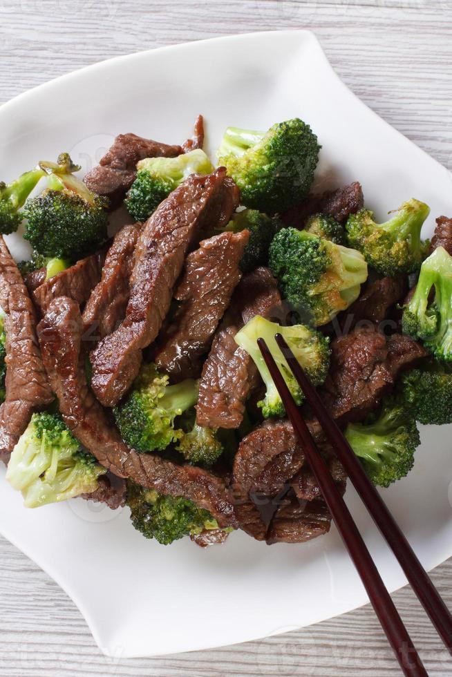 Aziatisch rundvlees met broccoli en eetstokjes. verticaal bovenaanzicht foto